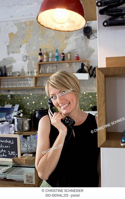 Mid adult woman on phone cafe