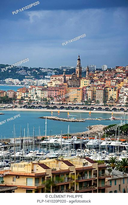View over the city and port of Menton and dark menacing rain clouds along the French Riviera, Provence-Alpes-Côte d'Azur, France