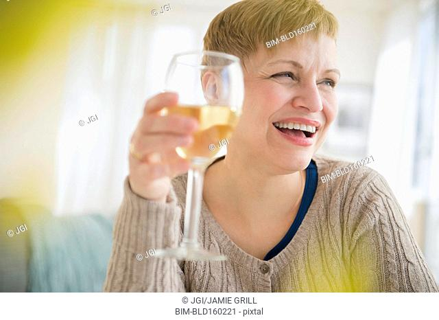 Caucasian woman drinking glass of wine in living room