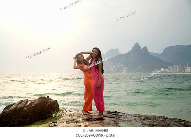 Portrait of two young women standing on rock, Ipanema beach, Rio De Janeiro, Brazil