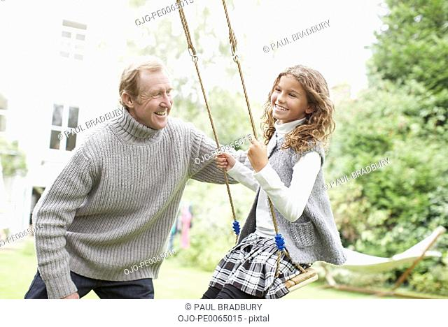Grandfather pushing granddaughter on swing