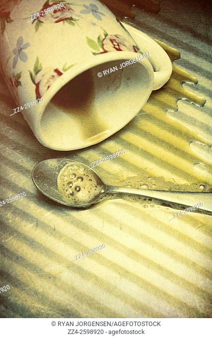 Fallen hot drink mug with spill puddle on kitchen bench. Kitchen drama