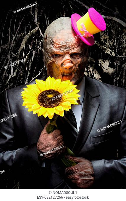Sad monster in business suit with sunflower