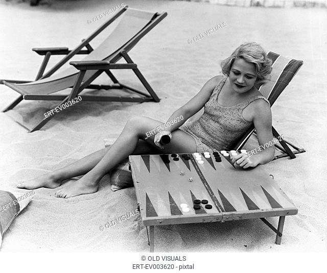 Woman playing backgammon on beach All persons depicted are not longer living and no estate exists Supplier warranties that there will be no model release issues
