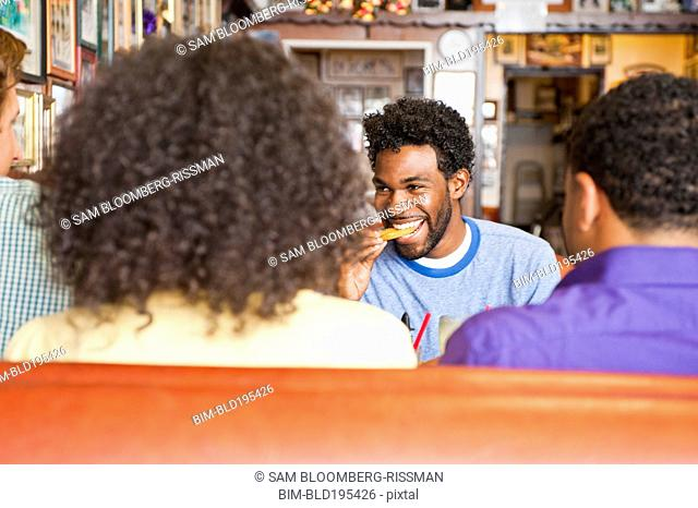 Smiling friends eating in diner booth