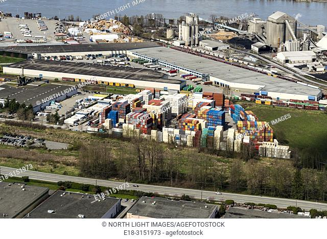 Canada, BC, Delta. Harbourlink container storage facility near the banks of the Fraser River. Cement factory in the background