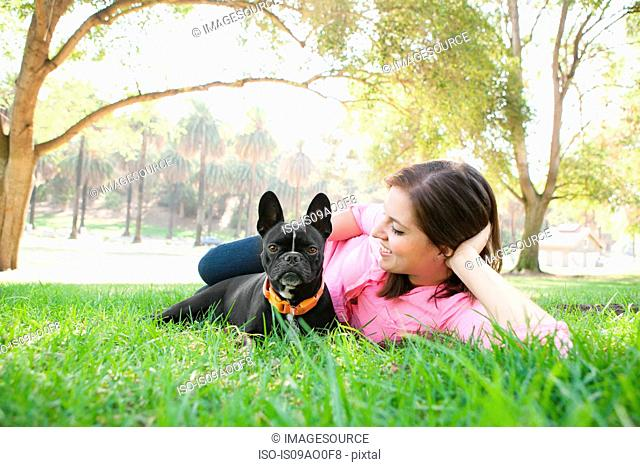 Portrait of young woman and dog lying in park together