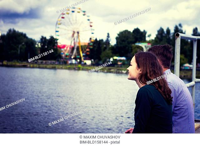 Couple standing at waterfront near ferris wheel