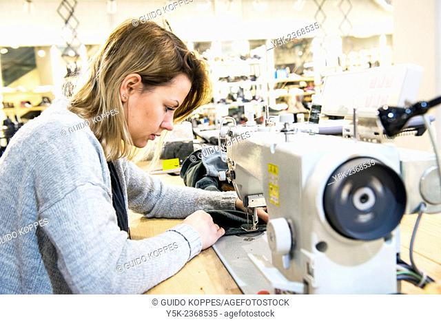 Tilburg, Netherlands. Young needlewoman buzzy shortening a jeans at her workstation in a fashion store for one of her customers