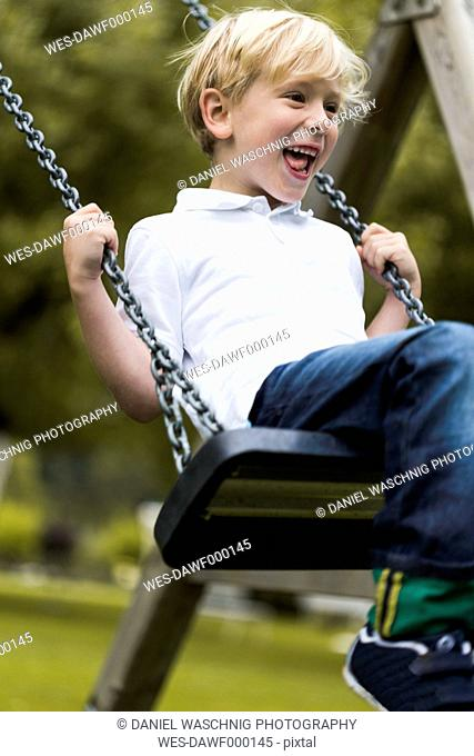 Portrait of little boy sitting on a swing