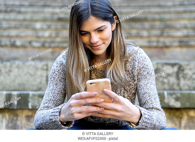 Young woman sitting on stairs outdoors using cell phone