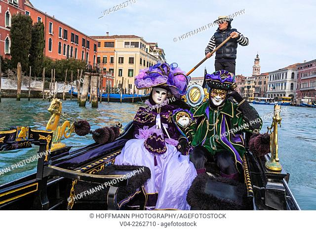 A masked couple in a gondola on the Grand Canal (Canale Grande) at the carnival in Venice, Italy, Europe