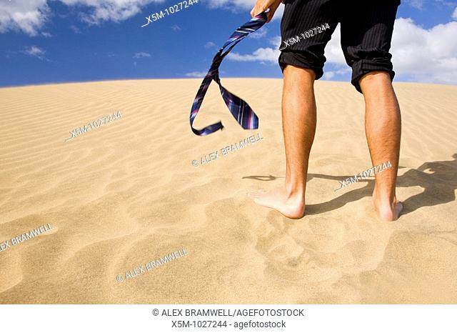 A businessman with his trousers pulled up and his tie in his hand, walking up a sand dune