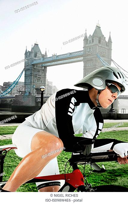 Cyclist with Tower Bridge in background, London, England