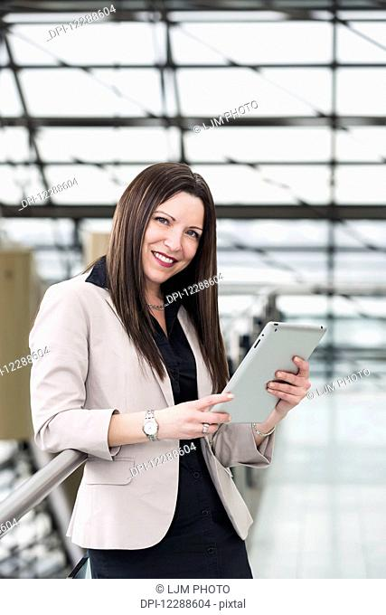 Mature business woman posing in the atrium of an office building and holding a tablet; Edmonton, Alberta, Canada