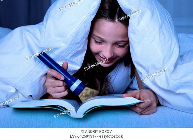 Girl Under White Blanket Using Flashlight While Reading Book At Night