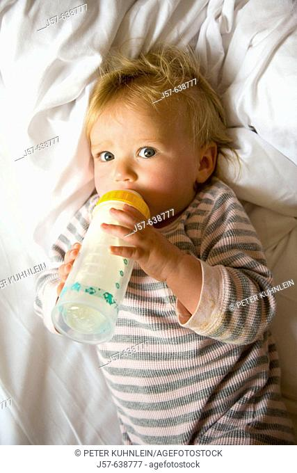 16 month old baby girl drinking a bottle of milk in the morning