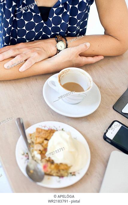 Midsection of woman sitting at table with coffee and dessert in cafe