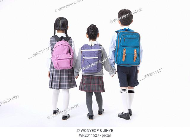 two girls and a boy standing next to each other