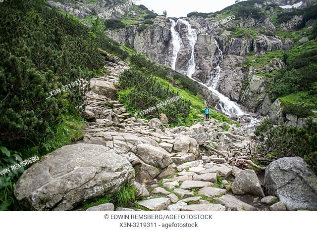 A woman hikes on a trail near Wielka Siklawa the highest waterfall in Poland in the Tatra National Park,Lesser Poland Voivodeship, Poland