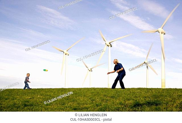 Man, boy play Frisbee at Wind Turbines