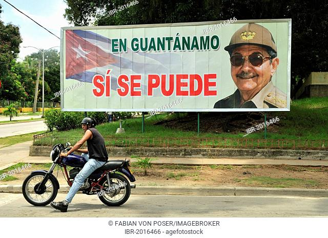 Motorcyclist in front of a sign with revolutionary propaganda, En Guantánamo si se puede, Guantánamo, Cuba, Caribbean