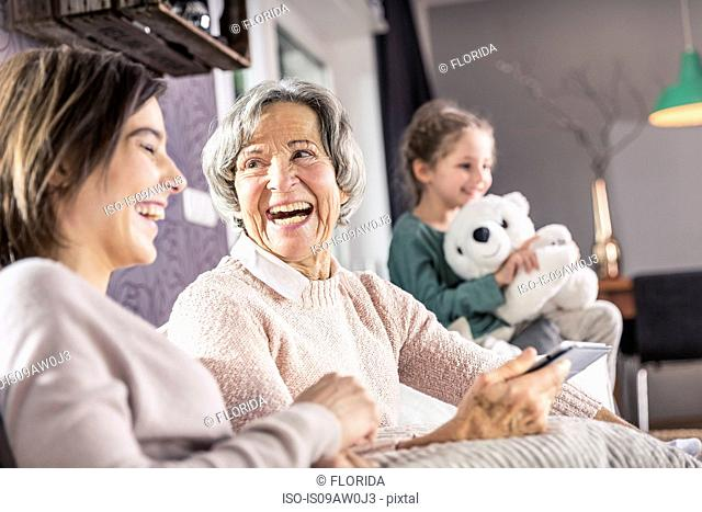 Senior woman, daughter and granddaughter laughing on sofa
