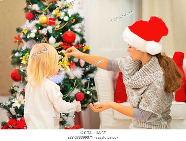 Mother and baby decorating Christmas tree