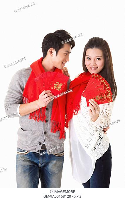 Young couple holding red envelope and smiling at the camera