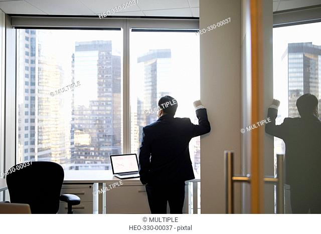Pensive businessman looking out office windows at highrise buildings