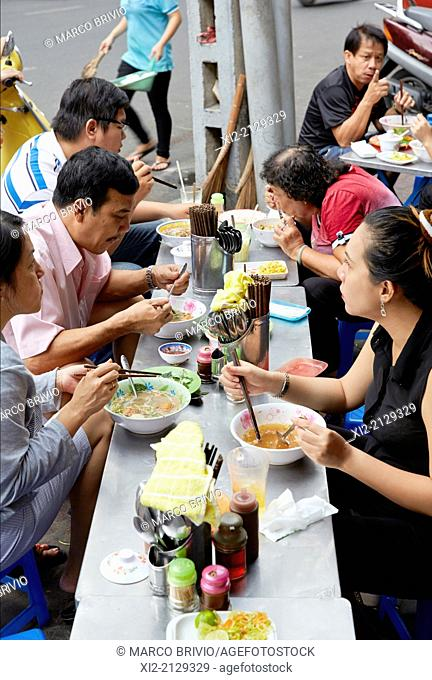 Vietnamese families having lunch in the streets of central Ho Chi Minh, Vietnam