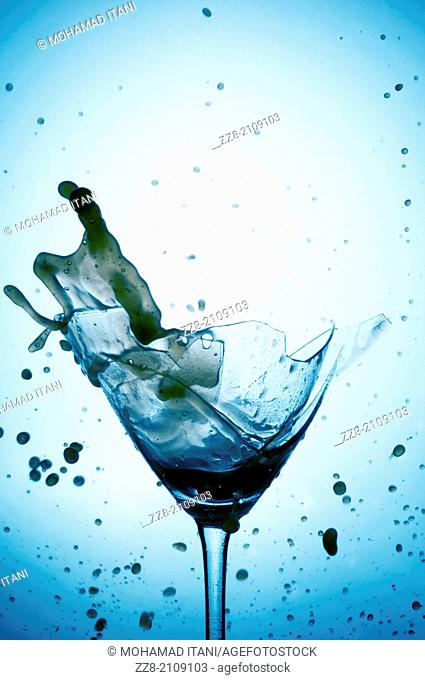 Powerful Splash breaking a martini glass , a conceptual image about alcohol addiction