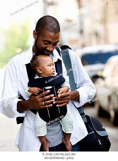 Mid adult man carrying son in baby sling