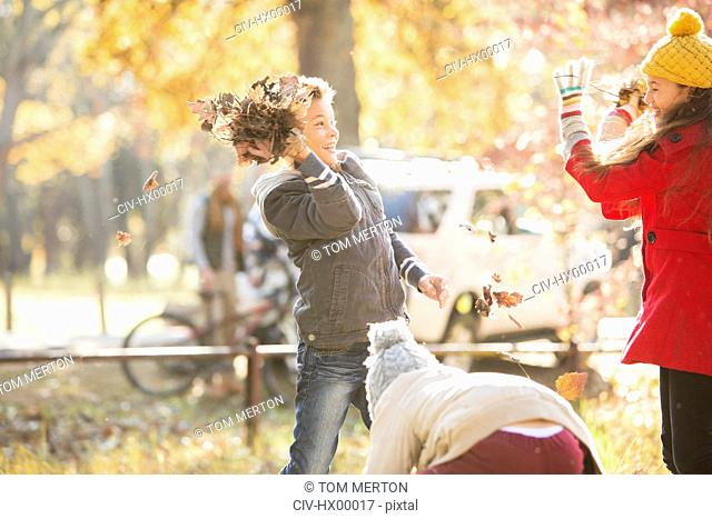 Boy throwing autumn leaves at girl in park