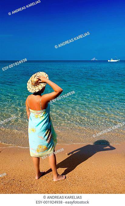 Young woman in pareo and straw hat looking into the deep blue se