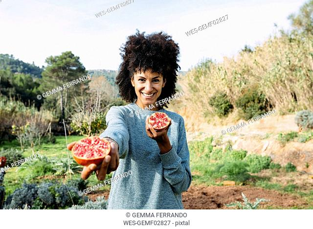 Woman holding halved pomegranate in an orchard
