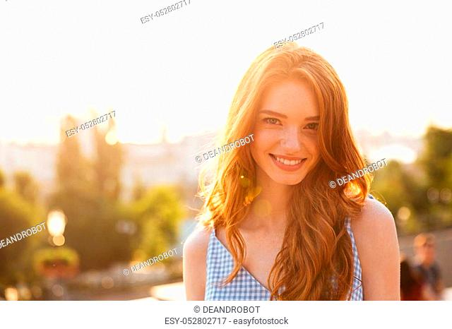 Close up portrait of a happy pretty redhead girl with long hair looking at camera while standing outdoors with a city view