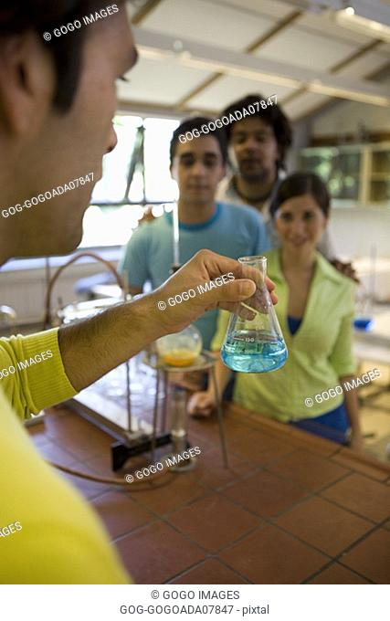 Science teacher demonstrating to students