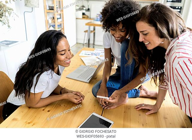 Three happy women with digital devices on table at home