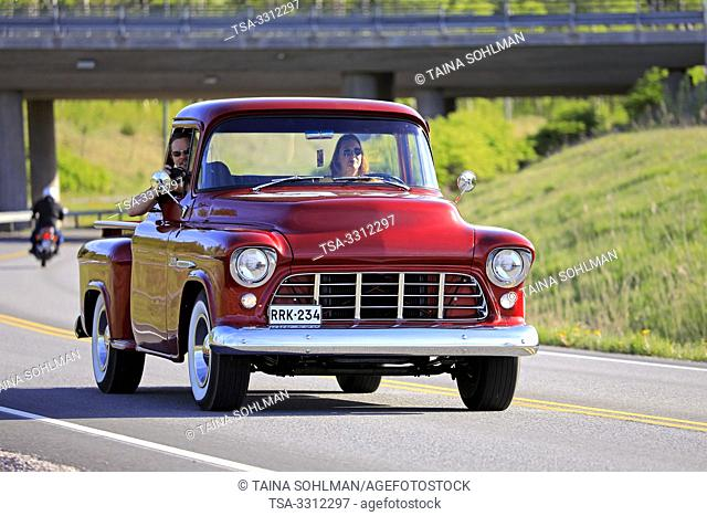 Salo, Finland. May 18, 2019. Woman drives a mid-1950s Chevy pickup, the man on passengers seat is photographing on Salon Maisema Cruising 2019