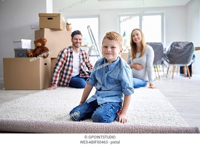 Portrait of happy family moving into new flat