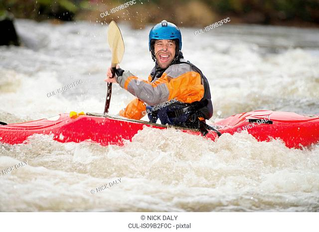 Happy male kayaker paddling River Dee rapids
