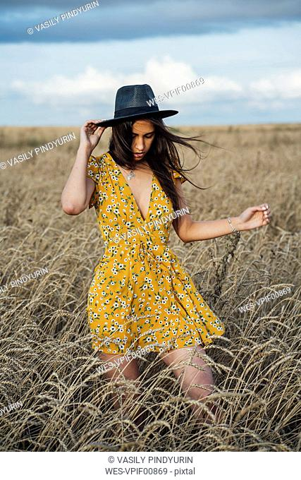 Young woman wearing summer dress with floral design and a hat dancing in corn field