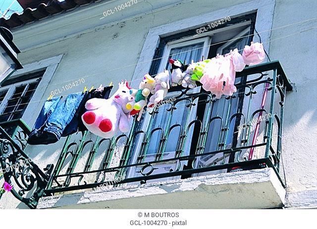Laundry and stuffed animals hanging on a clothesline in Lisbon, Portugal