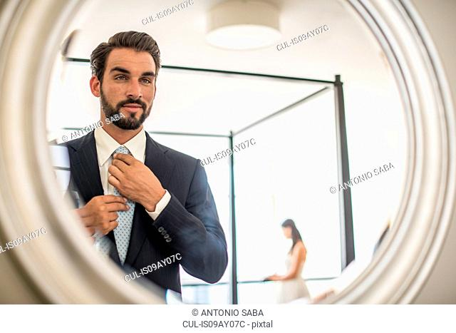 Mirror reflection of young businessman adjusting shirt and tie in hotel room, Dubai, United Arab Emirates