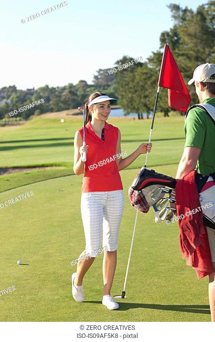 Young female golfer on golf course with caddy