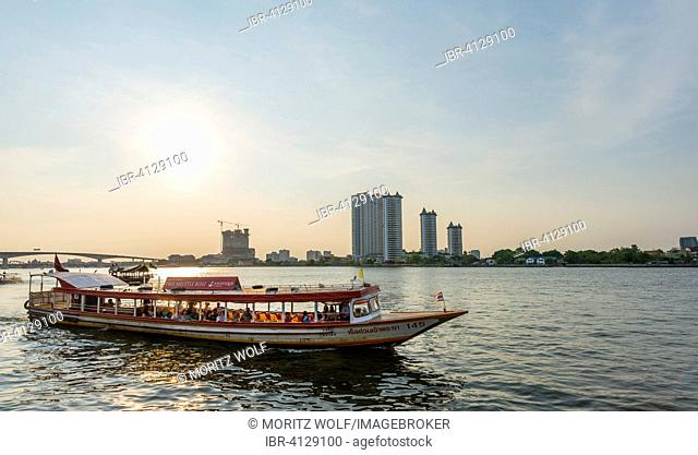 Tourist boat on the Mae Nam Chao Phraya river, skyscrapers behind, Bangkok, Thailand