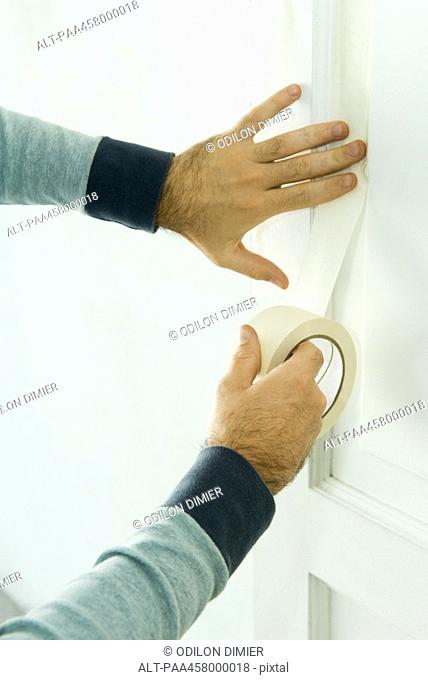 Man taping door with adhesive tape, cropped view of hands