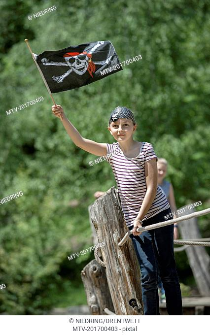 Girl standing on pirate ship and showing pirate flag in adventure playground, Bavaria, Germany