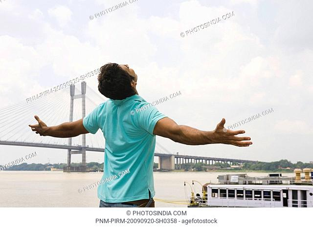 Man standing with his arms outstretched with a bridge in the background, Vidyasagar Setu, Hooghly River, Kolkata, West Bengal, India